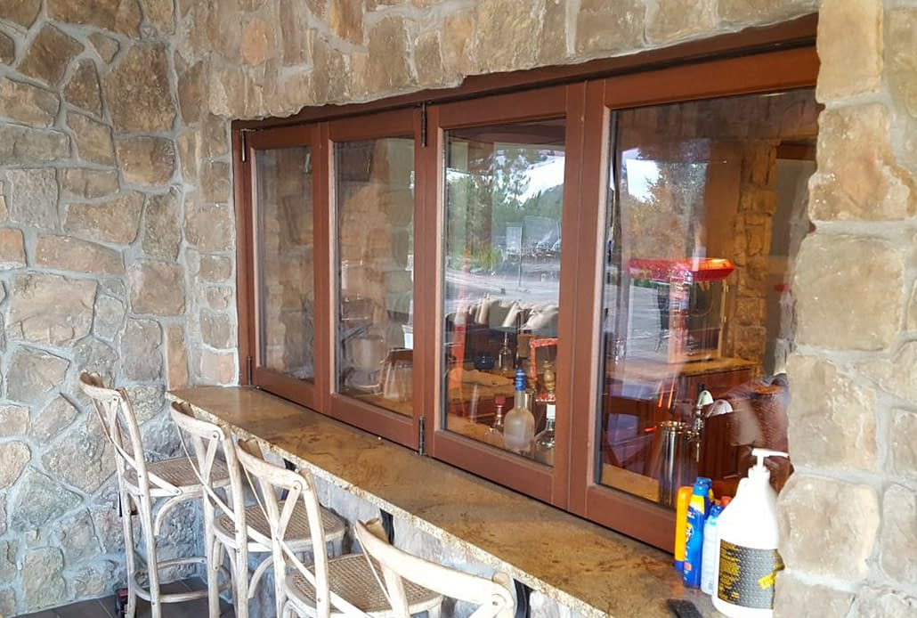 A custom four panel wood folding window allows access from the patio to the downstairs bar