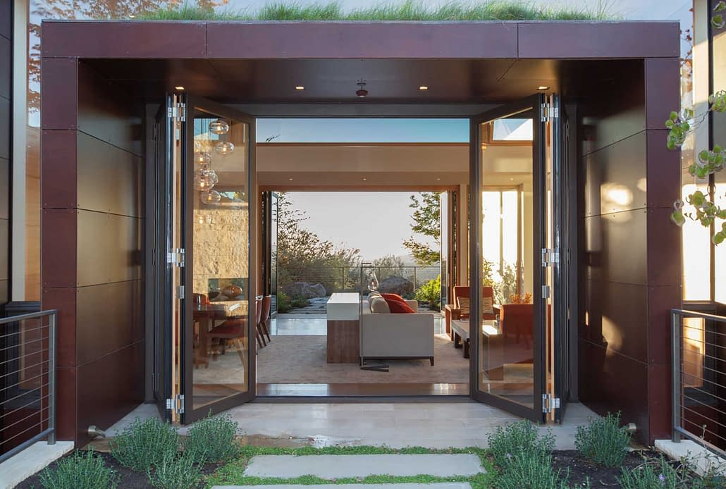 A four panel thermally broken steel folding door creates expansive openings in this modern villa