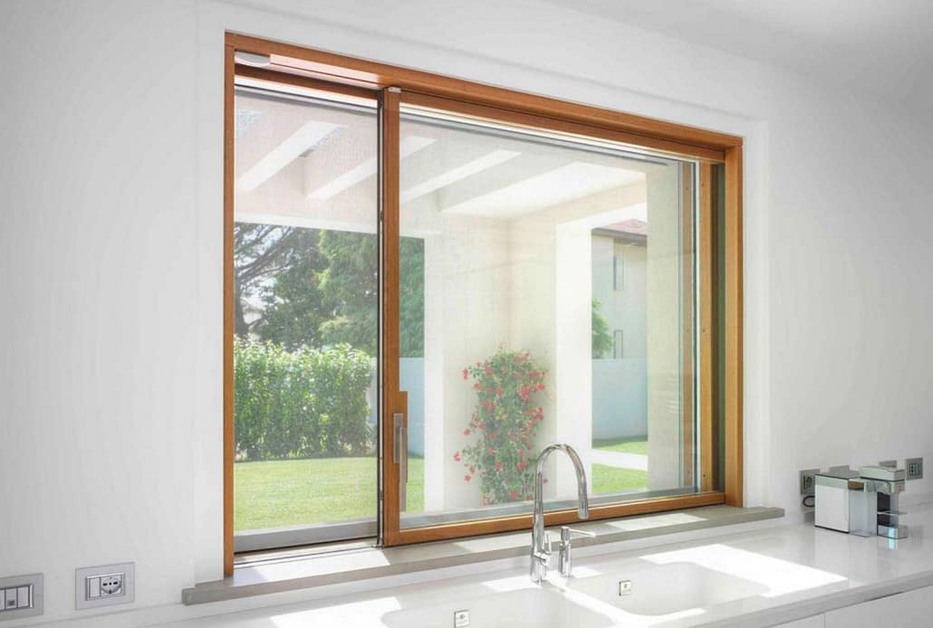 Carminati's minimal frame wood sliding window above the kitchen sink allows for unobstructed views of the backyard