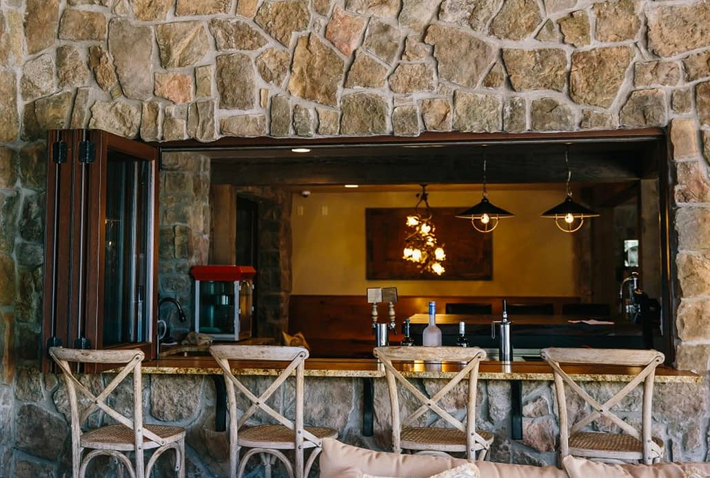 A four panel wood folding window opens the downstairs bar to the patio for easy entertaining
