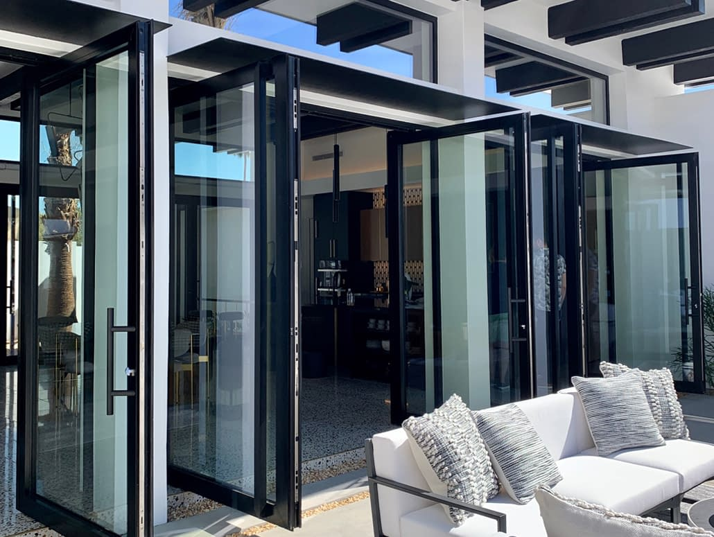Elegant matte black aluminum double-leaf pivot doors open up to the patio in this Palm Springs Villa. Partners: SPI Finestra