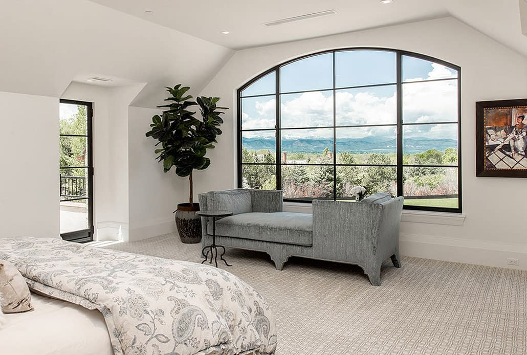 An oversized steel push out casement window with views of the Rocky Mountains