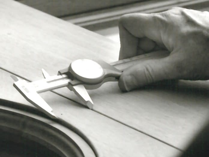 An individual performing measurements during the manufacturing of a custom wood window