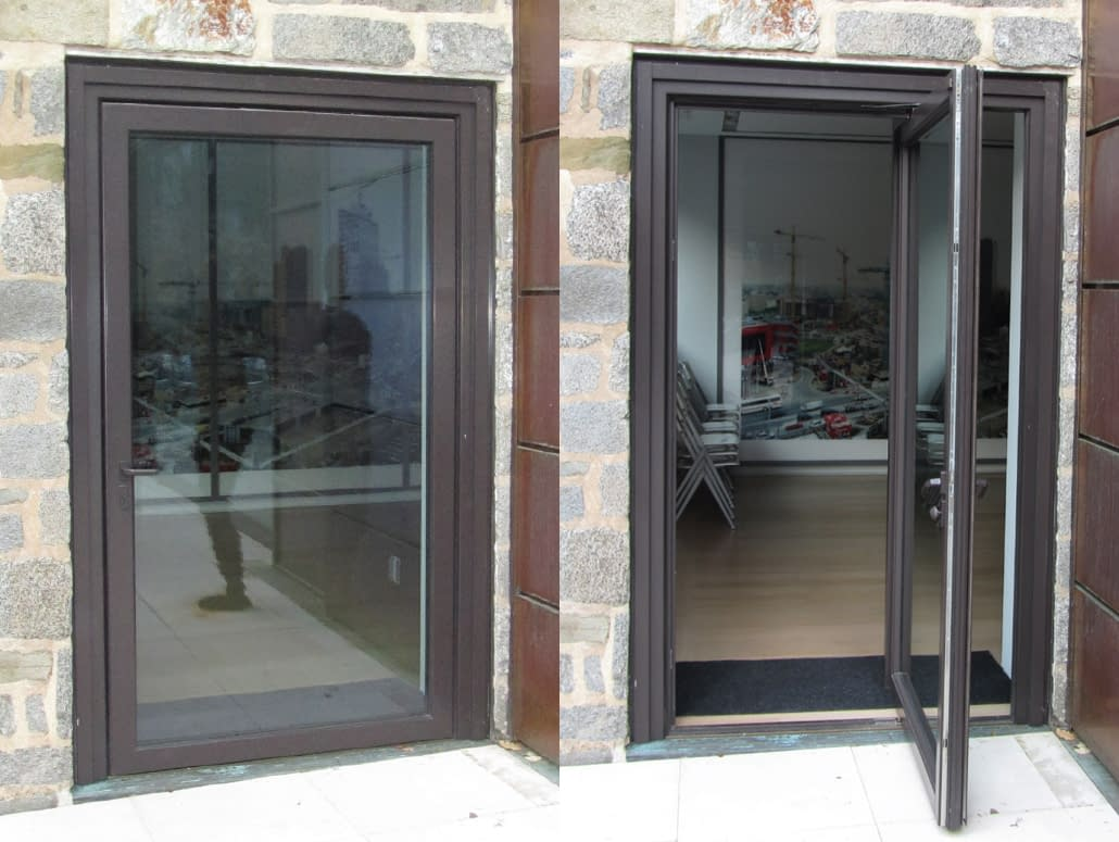 A bronze pivot door by Veranda View welcomes visitors to this contemporary home