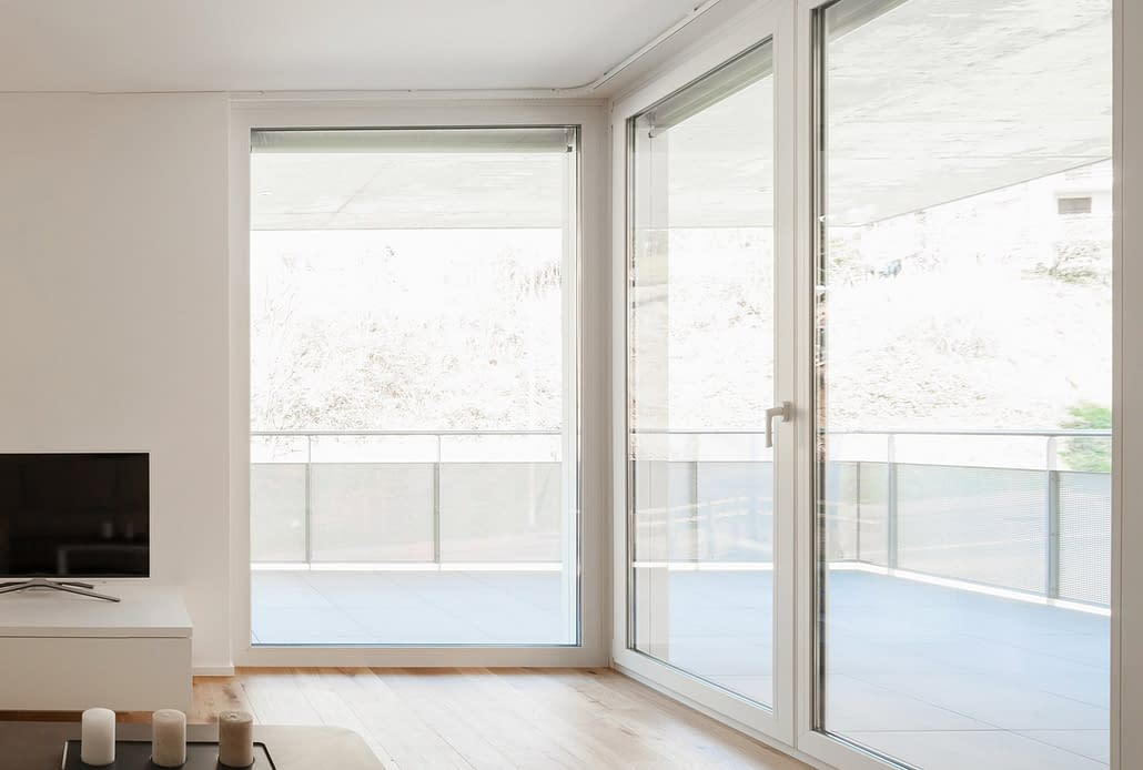 A custom oversized inswing door in a white finish with expansive glass brings in a lot of natural light