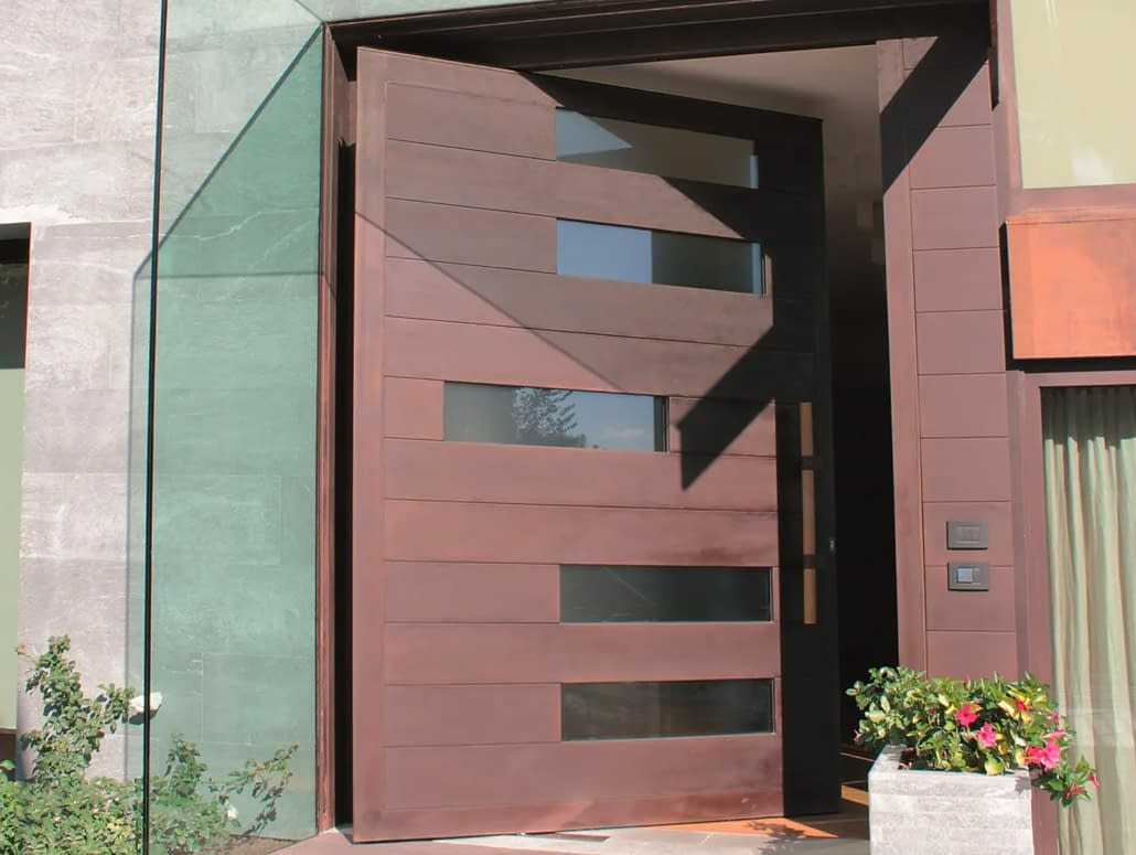 A wide pivot door in a cor-ten finish by Brombal sets the tone for the entrance of the house.